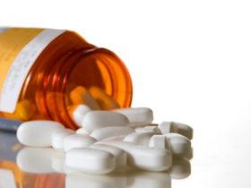 Uncapped amber medication bottle and tablets